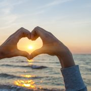 Händer som formar ett hjärta i solnedgången