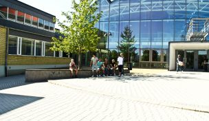 Entré Stenhammarskolan - 6-7 elever sitter utanför på stenmur