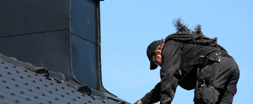 Sotare arbetar på skorstenen på ett hustak.