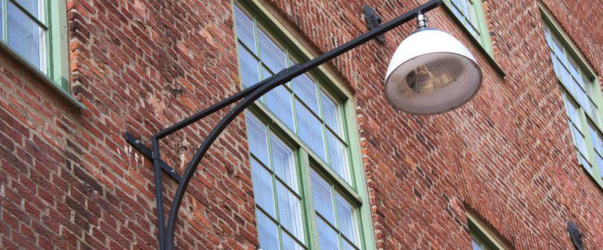 Fasad på röd tegelbyggnad med en stor armatur/belysning