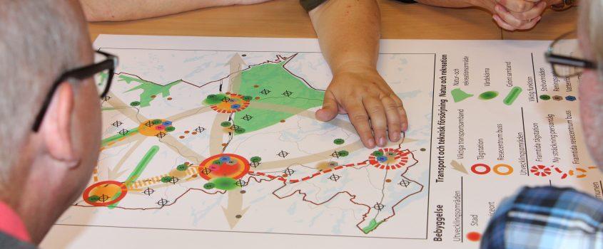 En karta som flera personer lutar sig över och diskuterar
