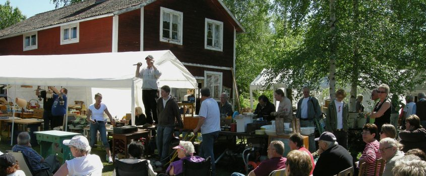 Sommarauktion - auktionsförättare och publik, antik och loppisprylar framför ett rödmålat hus