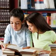 Två flickor sitter vid bord i bibliotek och läser tillsammans