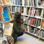 Ung kvinna letar efter böcker i ett bibliotek