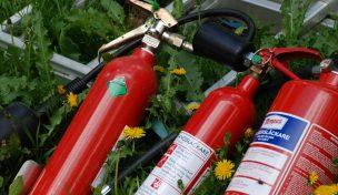 Olika brandsläckare och en stege ligger på gräs och maskrosor