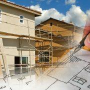 Hus med byggnadsställningar och hand som ritar byggritningar