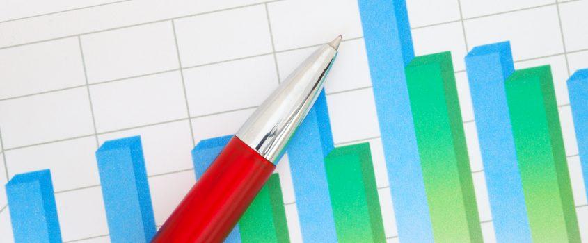 blågröna grafer på rutat papper och en röd penna