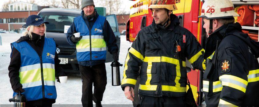 Två personer från Frivillig Resursgrupp med västar och två räddningstjänstpersonal vid brandbil