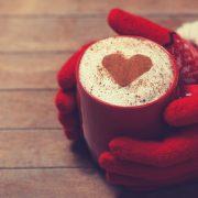 En kopp varm kaffe latte med kanelhjärta, vantbeklädda händer