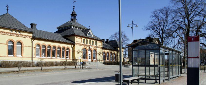 Framsida av Flens Järnvägsstation med busshållsplatser i förgrunden