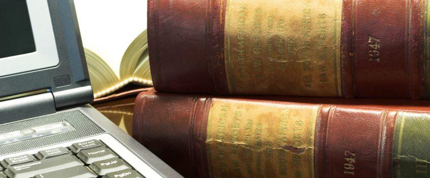 Juridiska böcker brevid en laptop.