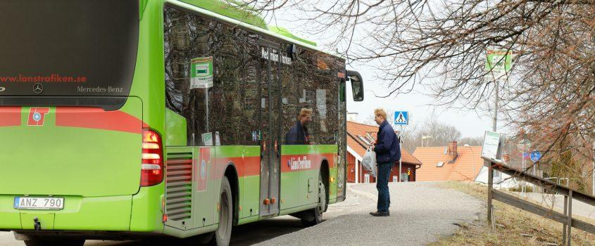 Passagerare förbereder sig för att borda en grön länstrafikbuss