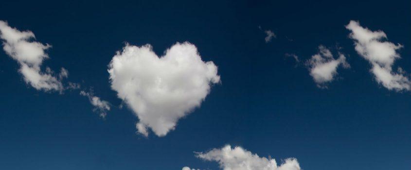 Blå himmel med moln - ett av dem format som ett hjärta