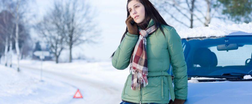 Ung kvinna vid bil ringer i mobiltelefon - en varningstriangel syns i bakgrunden