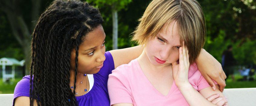 Två tonårstjejer tröstar varandra