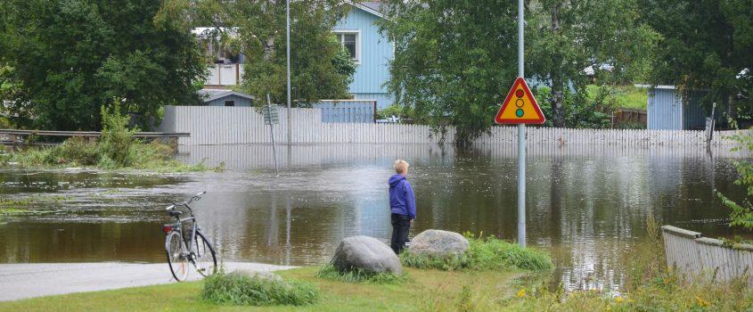 Pojke står och tittar på översvämmad villagata