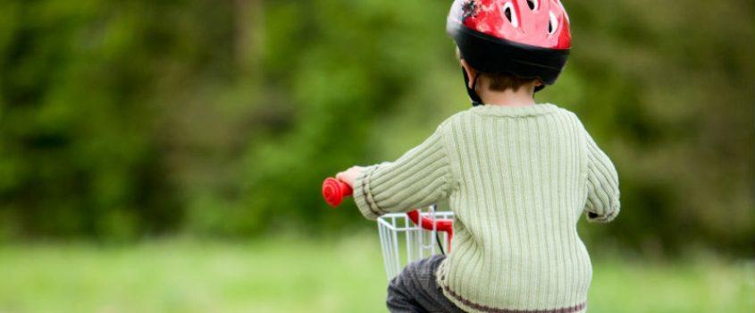 Pojke med cykelhjälm på cykel med stödhjul - cyklar på väg.