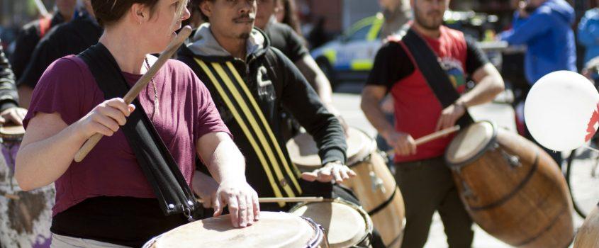 Går och trummar på afrikanska trummor på gatan