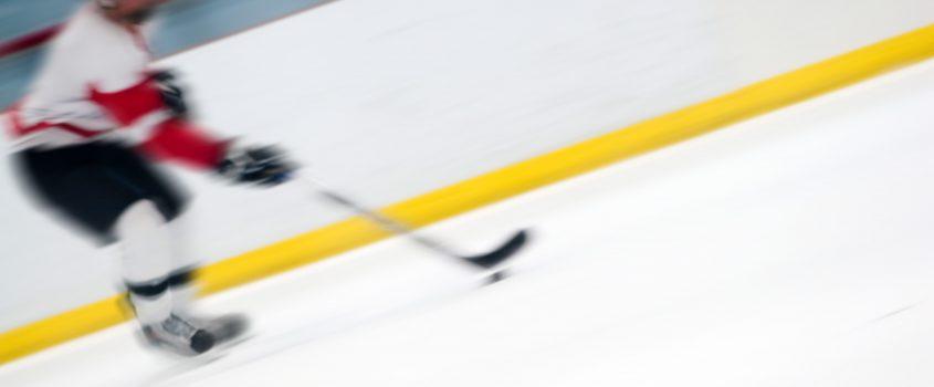 Ishockeyspelare som rör sig snabbt på en isrink