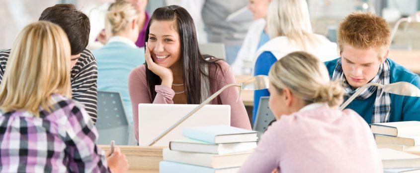Studerande ungdomar vid ett bord med böcker och datorer
