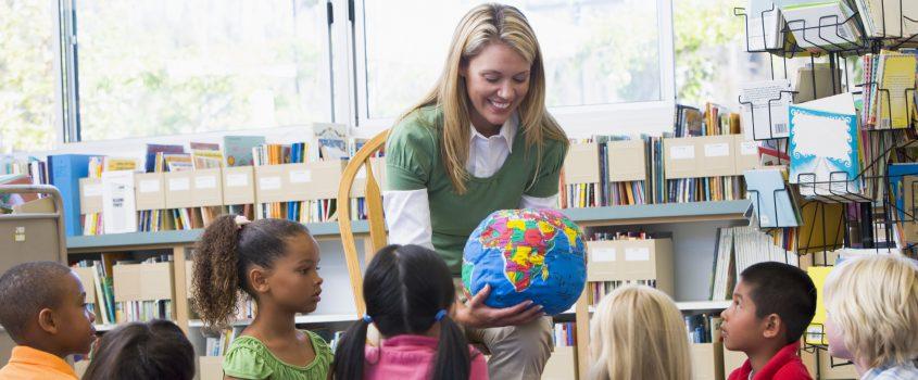 Lärare håller i en jordglob. Barn sitter runt omkring på golvet och lyssnar.