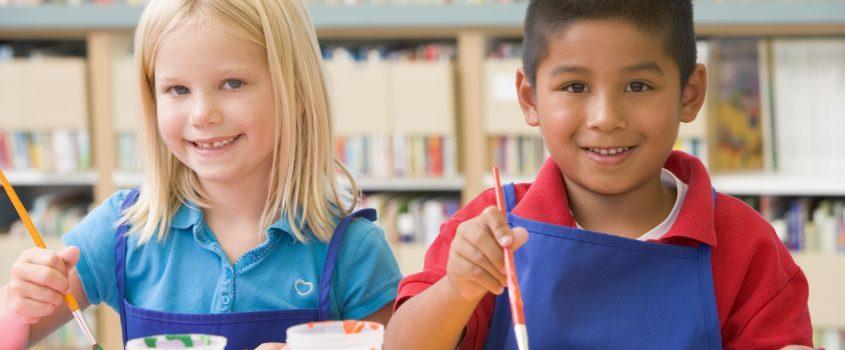 Barn med förkläden som målar