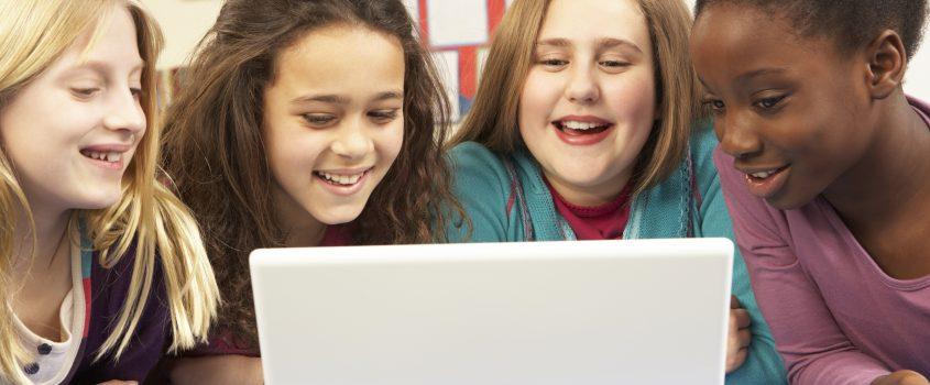 Fyra flickor som tillsammans tittar på en laptop
