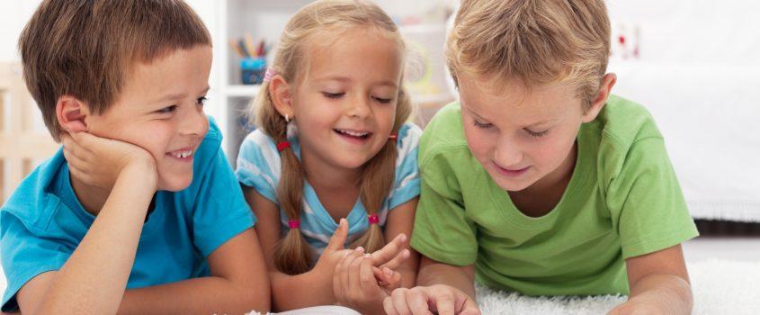 Tre barn som läser en bok