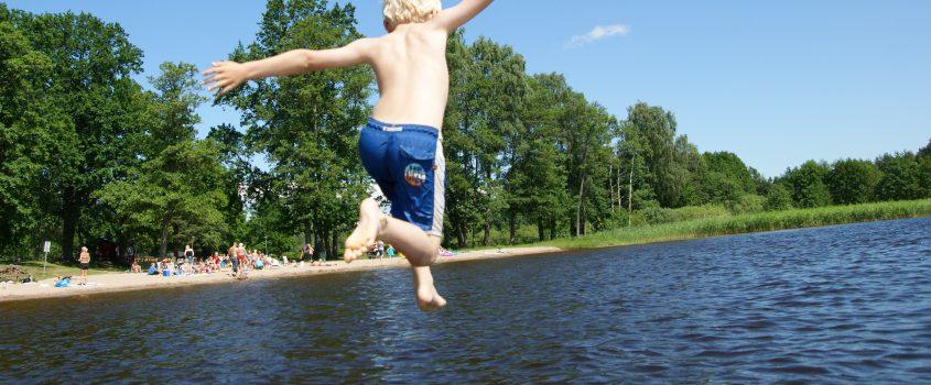 Pojke hoppar från brygga ner i sjö
