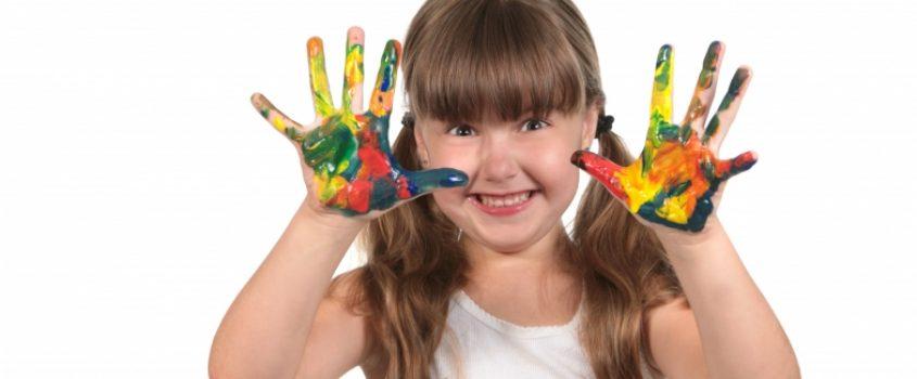 Glad flicka med färg på händerna.