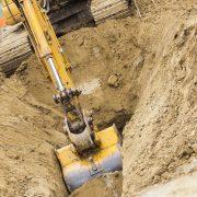 Grävmaskin som gräver i en sandgrop
