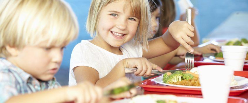 Barn som äter vid ett bord