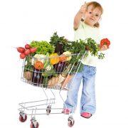 Flicka som gör tumme upp bredvid en kundvagn full av grönsaker.