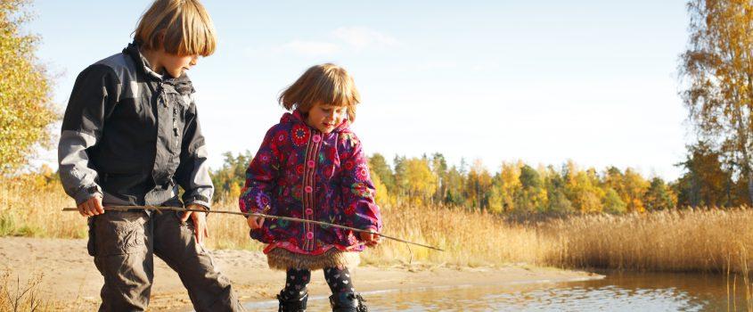 Pojke och flicka vid liten sjö.