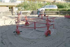 Lekplats med fjädergungor och en karusell med cyklar.