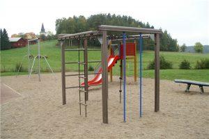 Lekplats med gungor, klätterställning och rutschkana.
