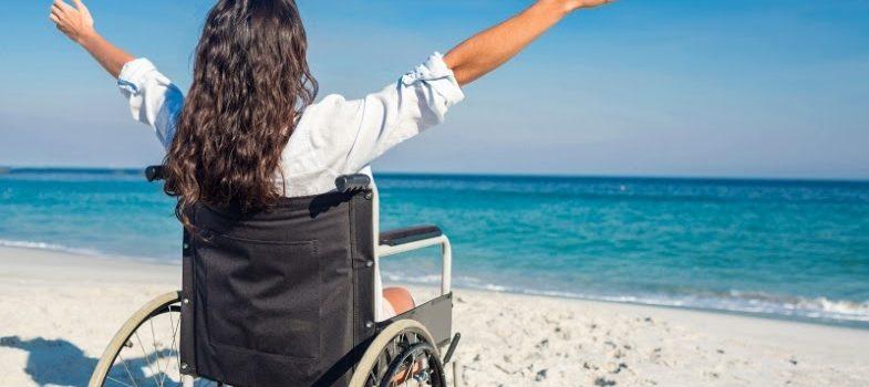 Kvinna i rullstul på strand