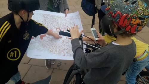 Barn med skateboards och karta över Flen