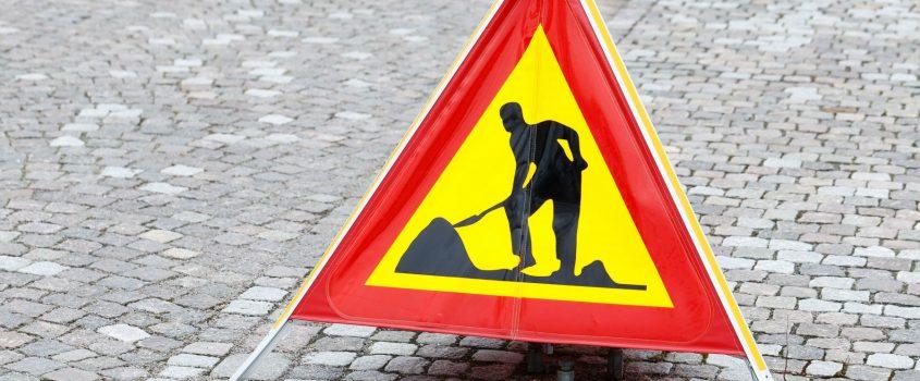 Varningsskylt - vägarbete pågår - på kullerstenslagd väg