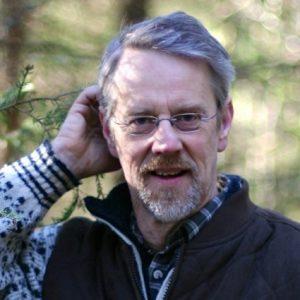 Ola Engelmark står i en skogsmiljö.