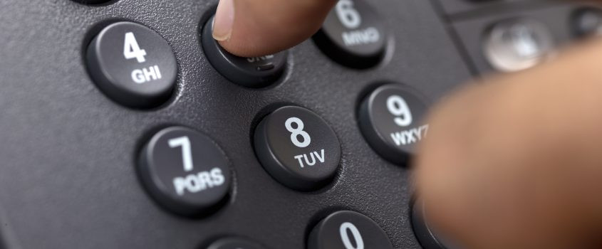 Hand som trycker in nummer på en telefon