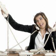Kvinna sitter med flera telefonlurar och jonglerar med dem