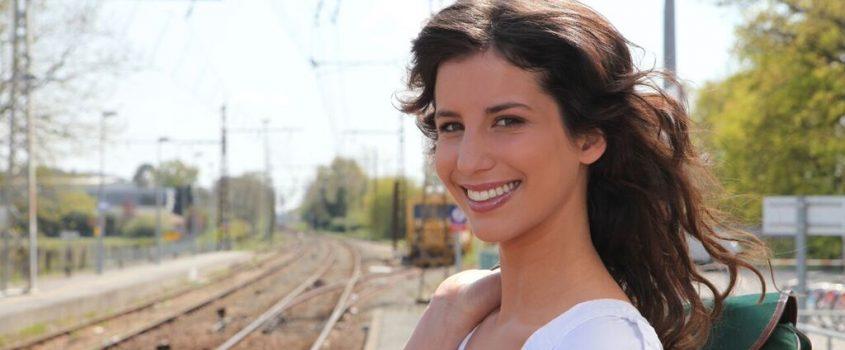 Kvinna som står intill ett järnvägsspår