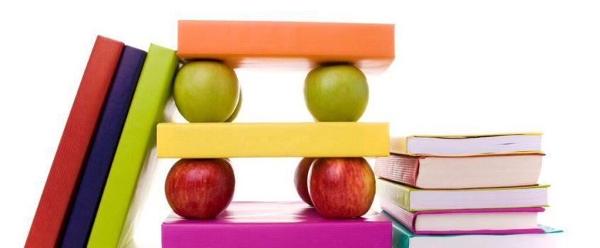 Böcker i olika färger uppställda tillsammans med röda och gröna äpplen
