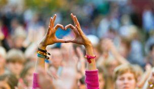 Publikhav där en person sträcker upp händerna och formar ett hjärta med pekfingarna och tummarna