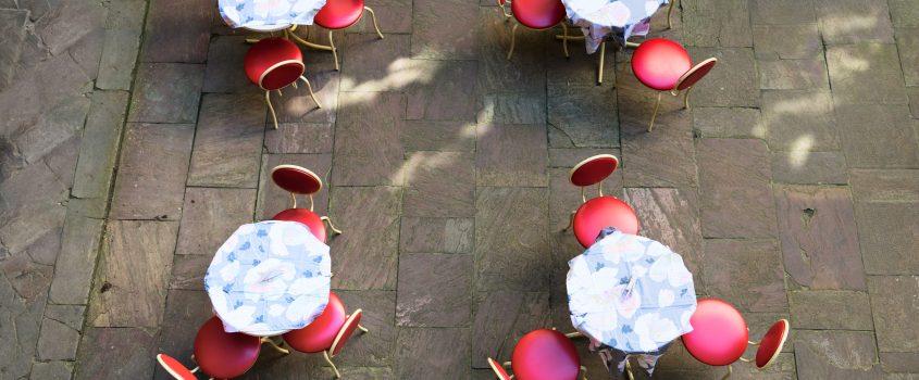 4 små runda bord med blå och vita dukar med tre röda kaféstolar runt vardera