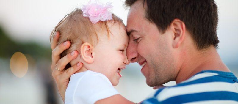 En pappa och en liten dotter som skrattar tillsammans
