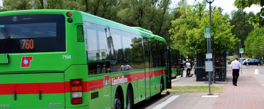 Grön buss vid busshållplats.