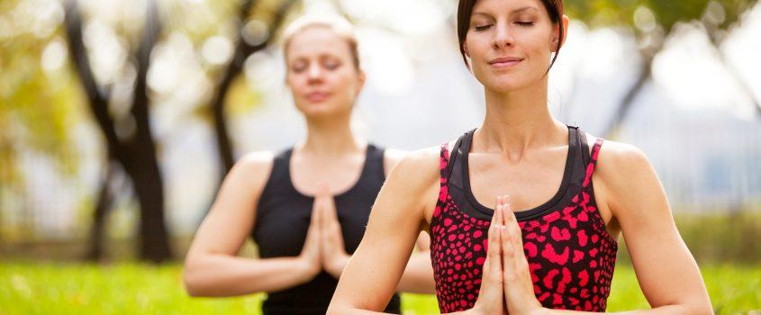 Två kvinnor som sitter i gräset med korslagda ben och mediterar