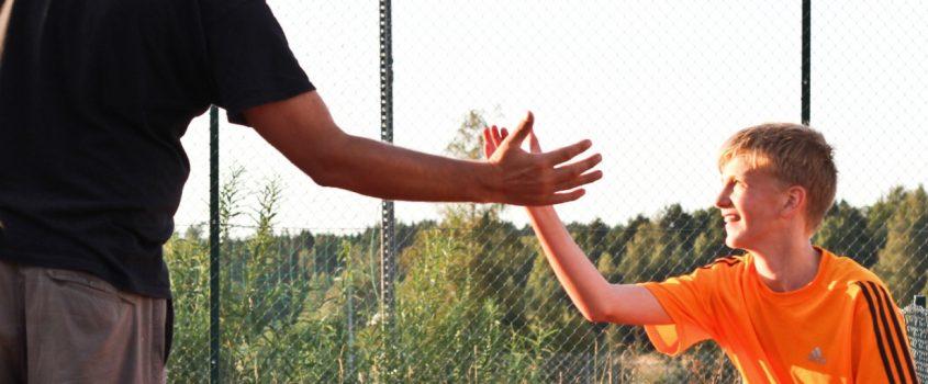 En vuxen man och en tonåring för high-five